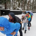 students form a train to get down the street in winter