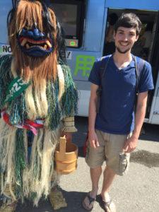 christopher cullum poses with namahage at akita international university