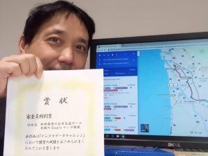 PDFで送った賞状を印刷し、Googleマップの画面前で掲げる豊田教授の写真