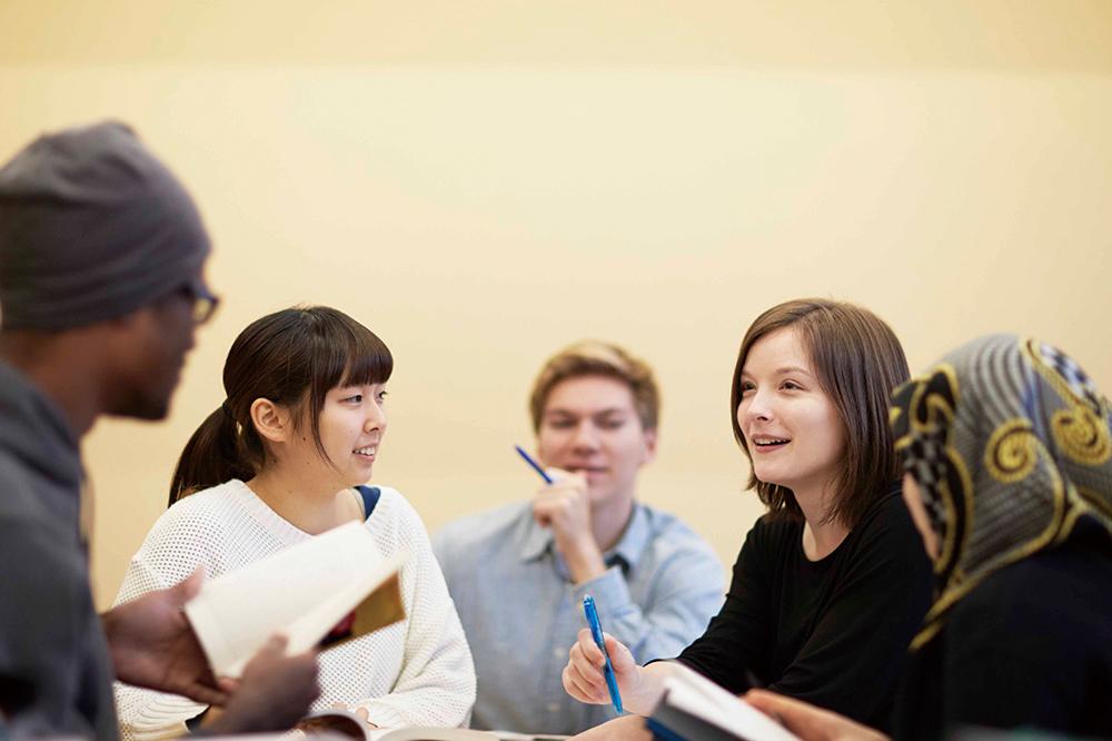 キャンパス内で会話を楽しむ学生たちの写真