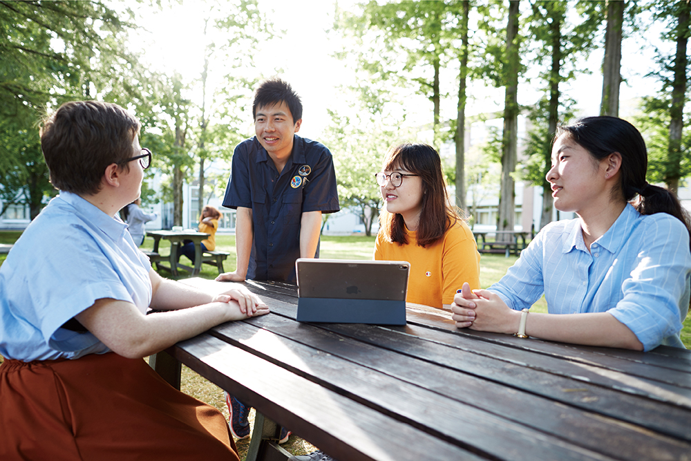 キャンパス内で談話する大学院生の写真
