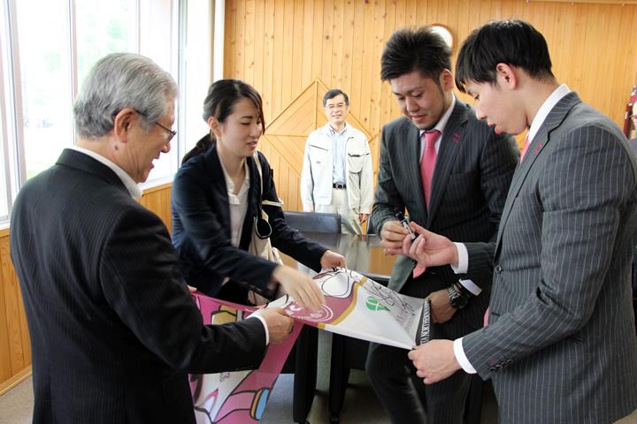 フラッグにサインをする田口選手(右から2番目)、中山選手(右端)、里村さん(左から2番目)