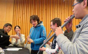 尺八の演奏体験をする留学生たちの写真