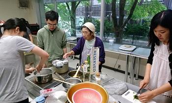 郷土料理を教わりながら調理している学生たちの写真