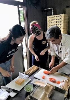 高橋さんの魚さばきに注目する学生の写真