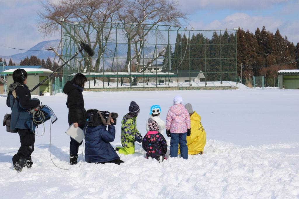 留学生と児童が共に雪像作りに挑戦している様子の取材風景