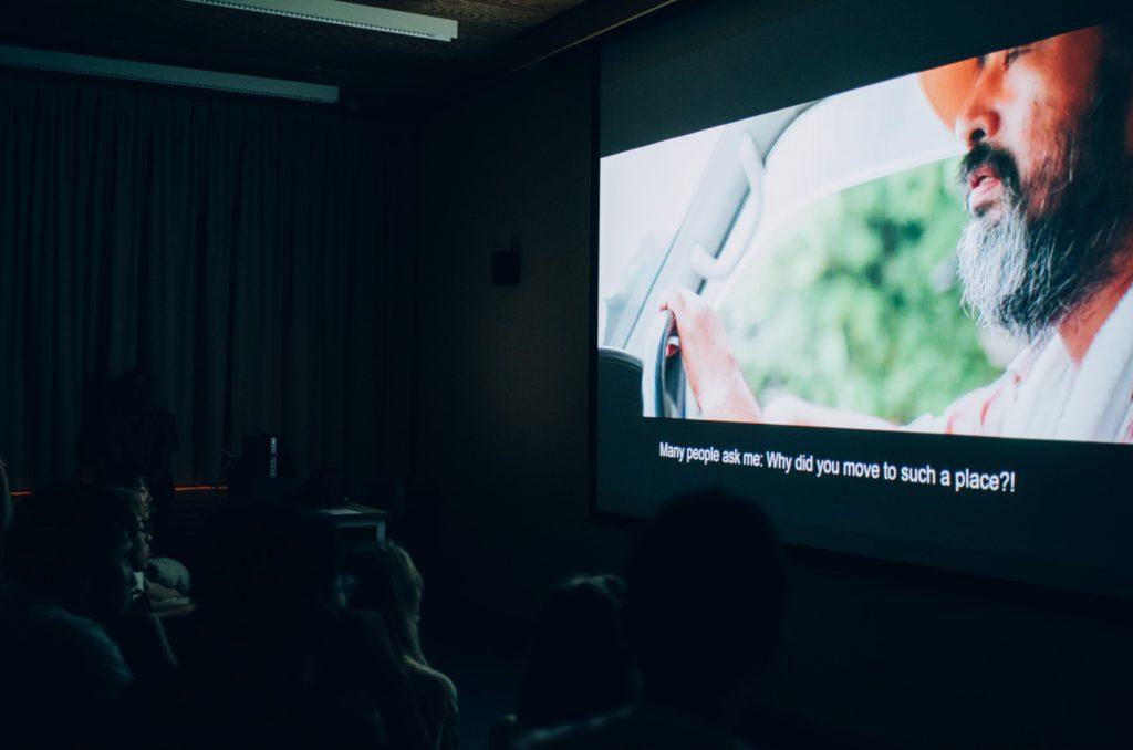 暗くした教室でスクリーンに動画を投影している写真