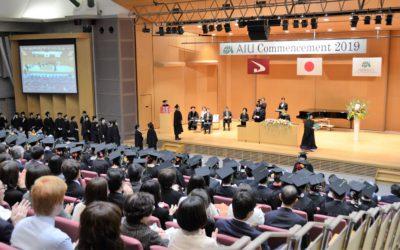 卒業式で、学生が列になり、壇上で学位記を授与される様子