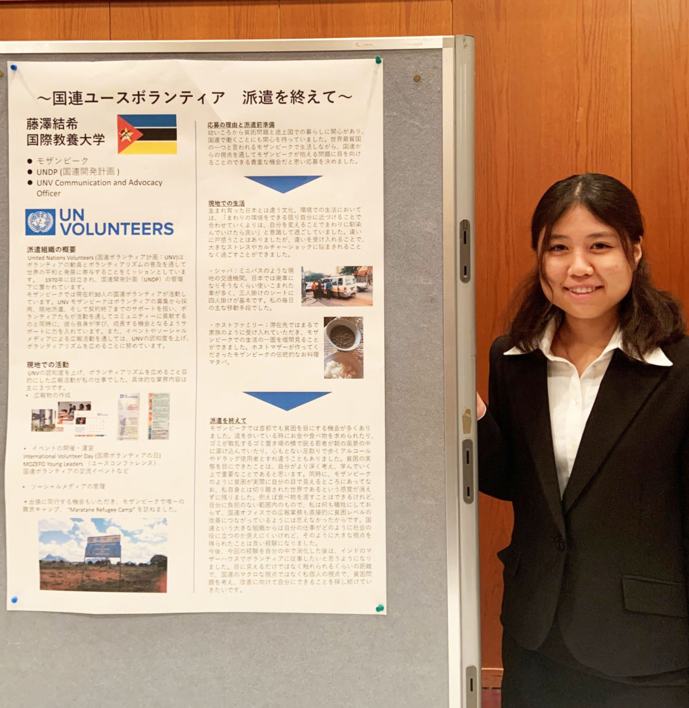 「国連ユースボランティア、派遣を終えて」のポスターを貼ったボード横で発表する様子