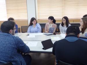 パソコンやタブレットを片手に、グループで話し合っている写真