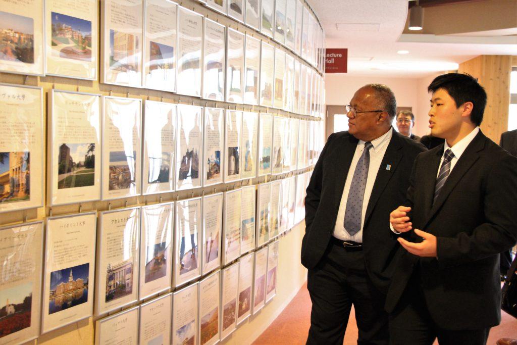 学内の廊下を歩きながら、学生と並んで説明を受ける大使の写真