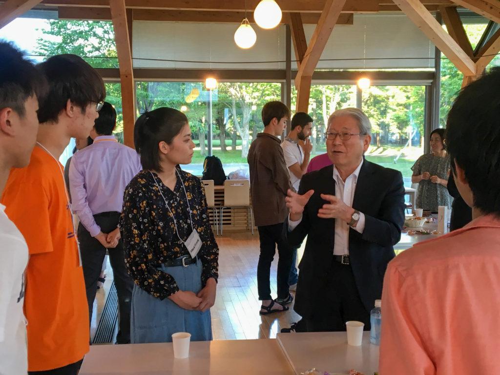 学生・教職員がテーブルごとに分かれて懇談している写真