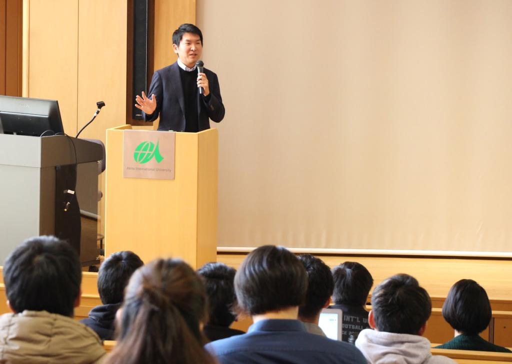 関山和秀氏が壇上から学生に向けて講演している様子