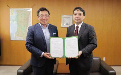 調印式にて覚書を一緒に持つトヨタカローラ秋田の加藤社長(左)と本学機構長