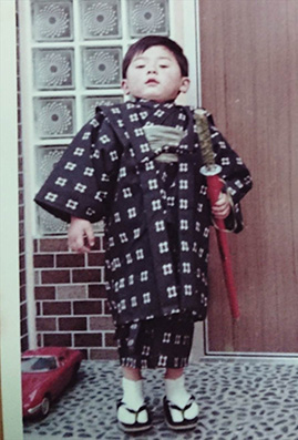 The childhood picture of Dr. MIZUNO wearing Kimono and red imitation sword on his waste