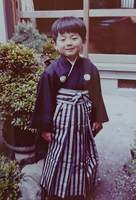 The childhood picture of Dr. MIZUNO wearing Hakama and standing at backyard