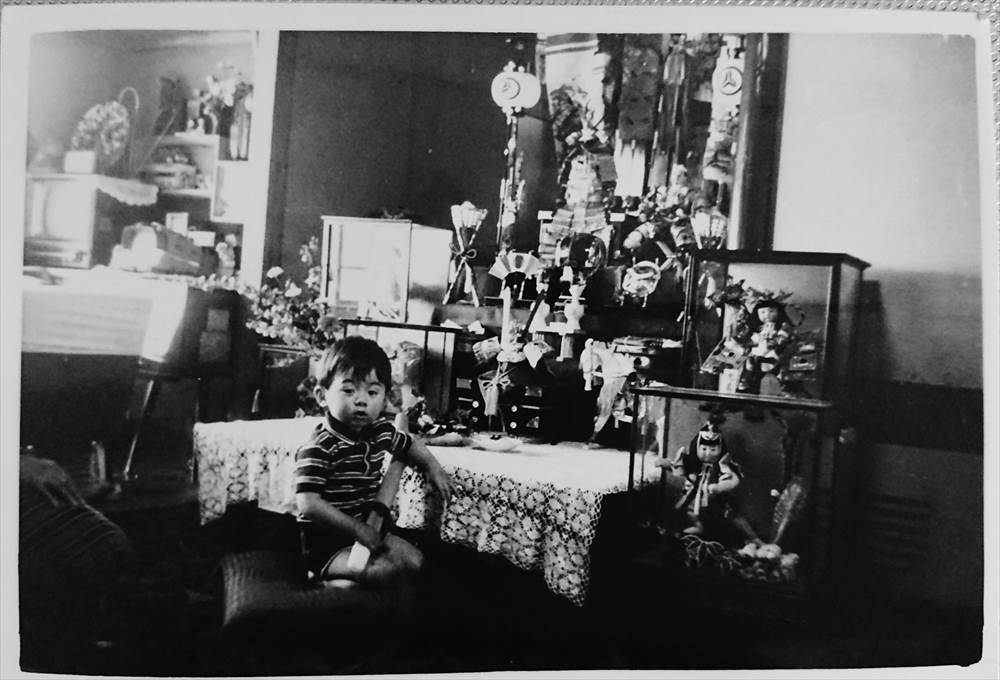 The picture of Dr. MIZUNO sitting in front of Japanese Boy's Festival decorations and dolls in his childhood