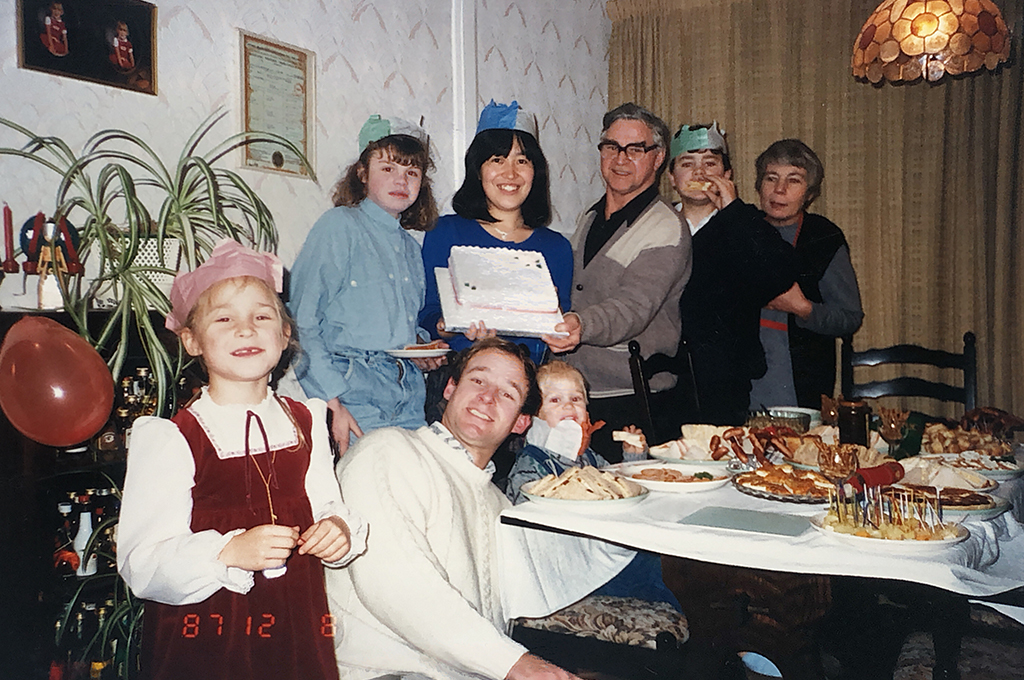 Picture of Dr. Abe holding her birthday cake and surrounded by her host family