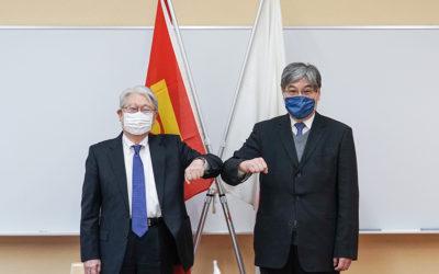 大使と鈴木学長が肘タッチをして記念写真を撮っている様子