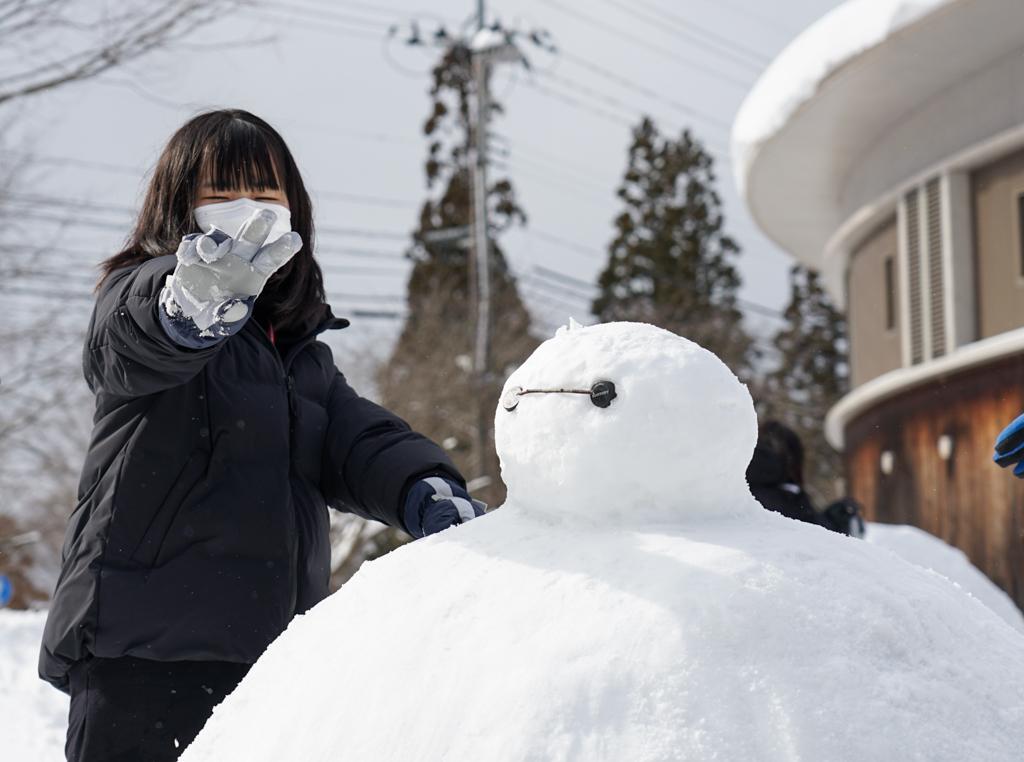 完成した雪像に触れVサインをしている学生
