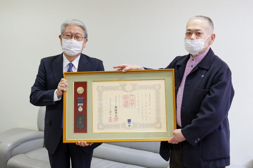 須田会長と鈴木学長が並んで紺綬褒章を見せている写真
