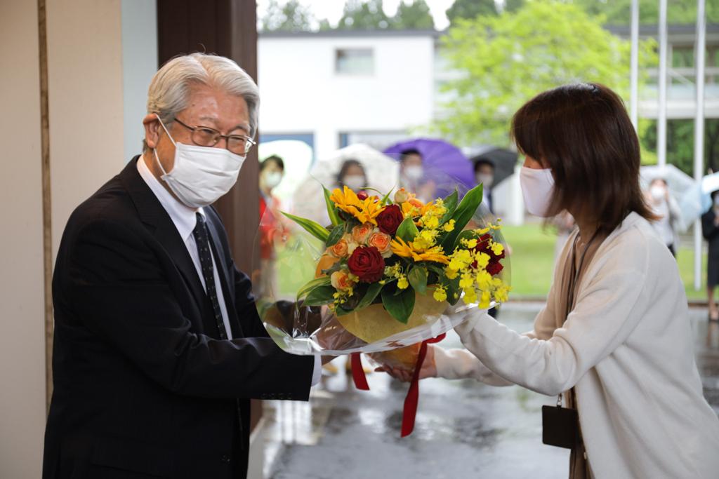 秘書が学長に花束を手渡している写真