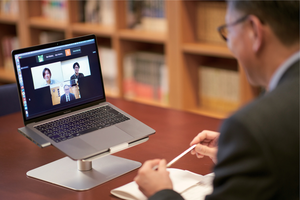 オンライン会議システムを使った座談会で談笑する3人の写真