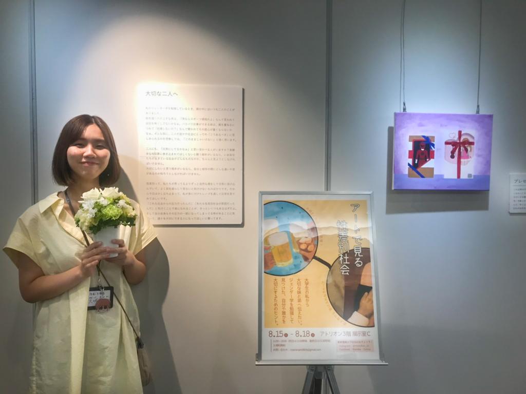 会場に設置した展覧会のポスターの前で、花を手に写る大城さん