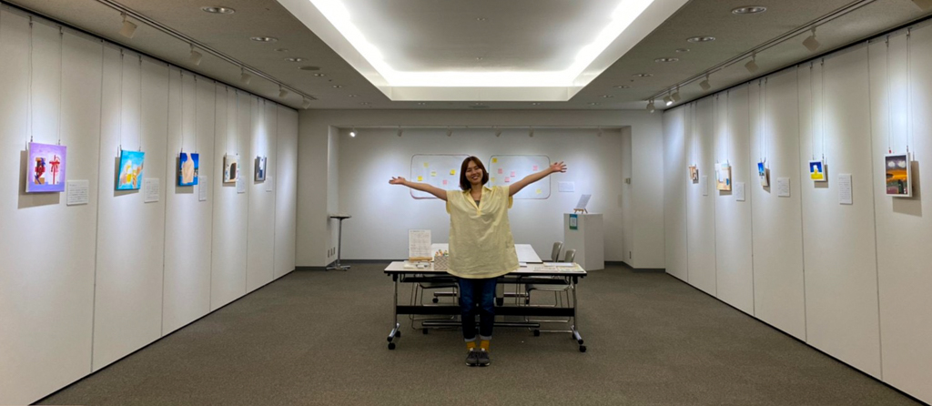個展の会場で、作品を紹介するように両手を広げる大城さん
