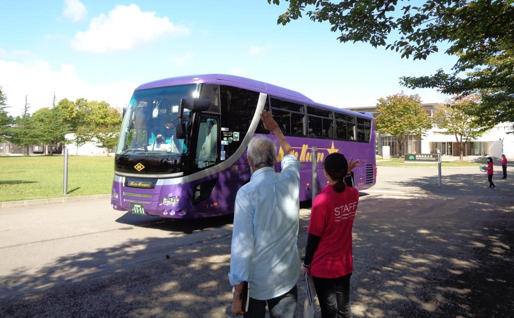 出発するシャトルバスに向かって手をふるカセム学長