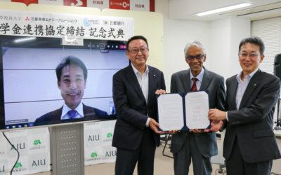 記念式典で証明した合意文書を手に取る4者の代表の集合写真