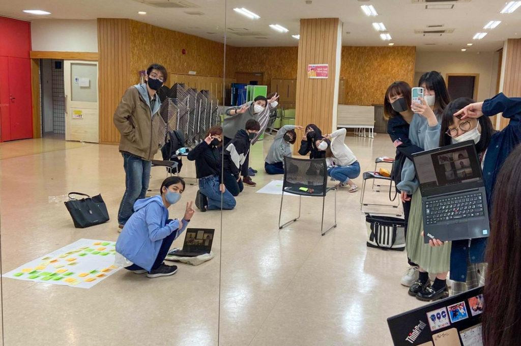 広い室内で打ち合わせする学生たちの写真。画面の中にはオンライン参加している学生の姿も。